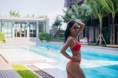 Young sexy woman in swimsuit stand near poolside wearing sunglasses at luxury hotel.  Stock Photo