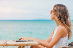 Young sexy woman using laptop on the beach. Freelance work. Young sexy woman freelancer in dress sitting at the table on ocean background, using laptop on the Royalty Free Stock Images