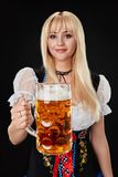 Young woman wearing a dirndl with beer mug on black background. Oktoberfest stock image