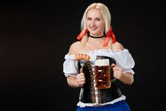 Young woman wearing a dirndl with beer mug on black background. Oktoberfest royalty free stock image