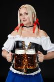 Young woman wearing a dirndl with two beer mugs on black background. Oktoberfest royalty free stock image