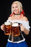 Young woman wearing a dirndl with two beer mugs on black background. Oktoberfest stock images
