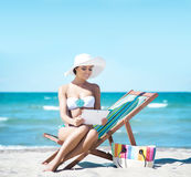 Young and sexy woman wearing a hat and a bikini on the beach Stock Photo