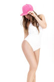 Young woman in white bodysuit and pink cap posing on white background Royalty Free Stock Images
