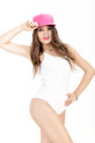 Young sexy woman in white bodysuit  and pink cap posing on white background Royalty Free Stock Images
