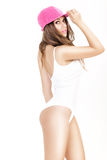 Young woman in white bodysuit and pink cap posing on white background Royalty Free Stock Photography