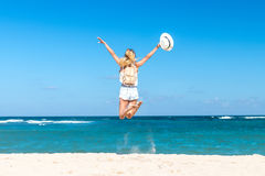 Young woman with white hat and luxury snakeskin python backpack jumping on white sand beach a tropical Bali island royalty free stock photos