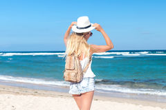 Young sexy woman with white hat and luxury snakeskin python backpack walking on white sand beach a tropical Bali island Royalty Free Stock Photography