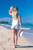Young woman with white hat walking on white sand beach a tropical Bali island at sunny day. Ocean cost. Young woman walking on white sand beach a tropical Bali stock photos