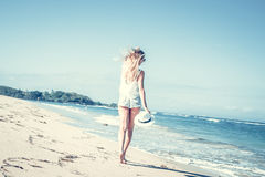 Young woman with white hat walking on white sand beach a tropical Bali island at sunny day. Ocean cost. Stock Image