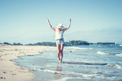 Young woman with white hat walking on white sand beach a tropical Bali island at sunny day. Ocean cost. Stock Photography