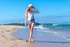 Young woman with white hat walking on white sand beach a tropical Bali island at sunny day. Ocean cost. Stock Photo