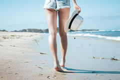 Young woman with white hat walking on white sand beach a tropical Bali island at sunny day. Ocean cost. Stock Photos