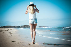 Young woman with white hat walking on white sand beach a tropical Bali island at sunny day. Ocean cost. Young woman walking on white sand beach a tropical Bali stock image