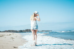 Young woman with white hat walking on white sand beach a tropical Bali island at sunny day. Ocean cost. Young woman walking on white sand beach a tropical Bali stock photography