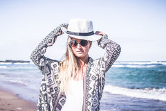 Young woman with white hat walking on white sand beach a tropical Bali island at sunny day. Ocean cost. Young woman walking on white sand beach a tropical Bali stock photo