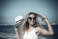 Young woman with white hat walking on white sand beach a tropical Bali island at sunny day. Ocean cost. Royalty Free Stock Photography