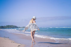 Young woman with white hat walking on white sand beach a tropical Bali island at sunny day. Ocean cost. Young woman walking on white sand beach a tropical Bali royalty free stock images