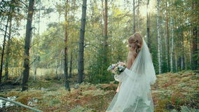 Young sexy woman in white lingerie with long veil standing in autumn forest.