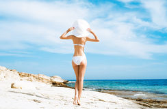 Young and sexy woman in a white swimsuit on the beach Royalty Free Stock Photography