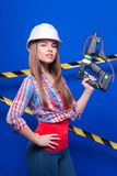 Young sexy worker girl in chechered shirt, white helmet and jean. Isolated on blue, young sexy brunette caucasian worker girl in chechered shirt, snickers and Royalty Free Stock Image