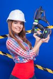 Young sexy worker girl in chechered shirt, white helmet and jean. Isolated on blue, young sexy brunette caucasian worker girl in chechered shirt, snickers, white Stock Image