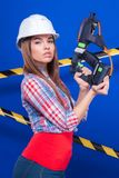 Young sexy worker girl in chechered shirt, white helmet and jean. Isolated on blue, young sexy brunette caucasian worker girl in chechered shirt, snickers, white Royalty Free Stock Photography