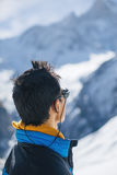 Young Sherpa looking at one of summits. Profile portrait of young Sherpa wearing protective sunglasses in Himalayas Royalty Free Stock Photo