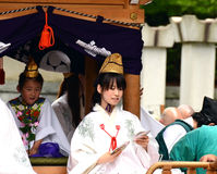 Young shinto priestess distributing good luck charms during Aoba festival stock photography