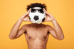Young shirtless african man covering head with a foot ball stock photography