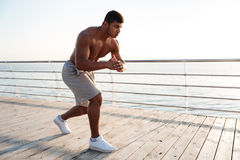 Young shirtless afro american sportsman doing squats on the pier stock image