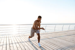 Young shirtless afro american sportsman doing squats on the pier stock photos