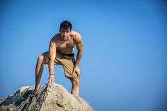 Young shirtless athletic man climbing on rock by Royalty Free Stock Photos