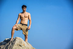 Young shirtless athletic man climbing on rock by Royalty Free Stock Photo
