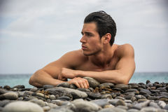 Young shirtless athletic man laying down on pebbles Stock Photography