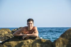 Young shirtless athletic man leaning on rock by Stock Images
