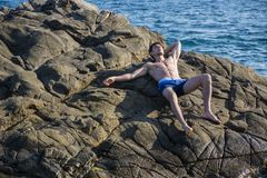 Young shirtless athletic man leaning on rock by Stock Photography