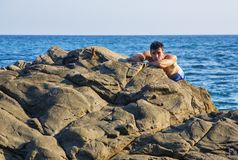 Young shirtless athletic man leaning on rock by Royalty Free Stock Photo