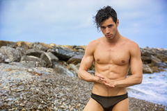 Young shirtless athletic man standing in water by ocean shore Royalty Free Stock Images