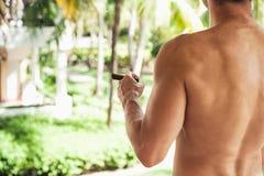 Young shirtless European man smokes cigar Stock Photos