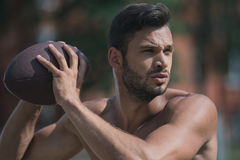 Shirtless handsome male football player with ball