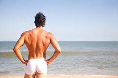 Young shirtless man on the beach stock image