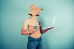Young shirtless man with cup and laptop Stock Image