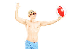 Young shirtless man playing with a beach ball. Isolated on white background Stock Photos