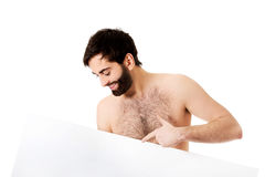 Young shirtless man pointing on empty banner. Royalty Free Stock Photos