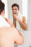 Young shirtless man with reflection brushing teeth Royalty Free Stock Image
