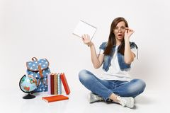 Young shocked bewildered woman student keeping hand on glasses hold pencil notebook sitting near globe backpack, school stock images