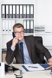 Young shocked businessman is phoning in the office Stock Image