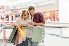young shocked couple with paper bags looking at smartphone in shopping royalty free stock photos