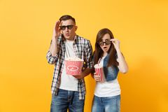 Young shocked couple woman man in 3d glasses watching movie film on date holding bucket of popcorn plastic cup of soda. Young shocked couple women men in 3d stock photo
